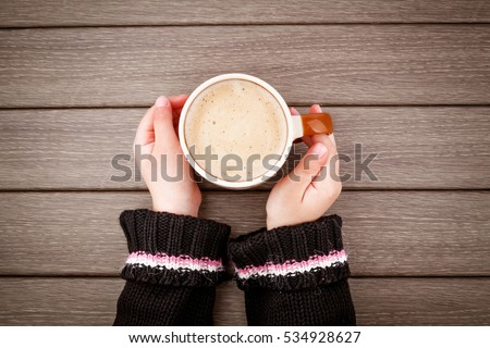 Little girl hand holding cup of hot coffee on wooden table