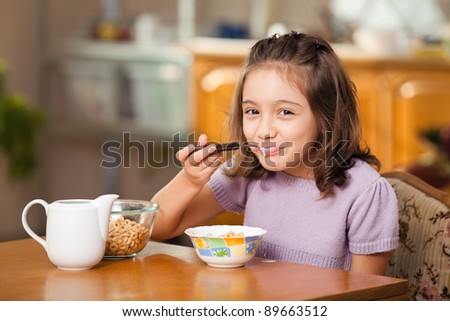 little girl having breakfast: cereals with milk