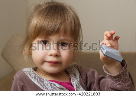 Little girl holding a toy block