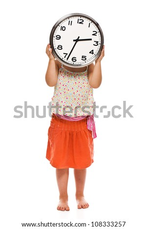 Little girl holding a wall clock in his hand. Studio shot.