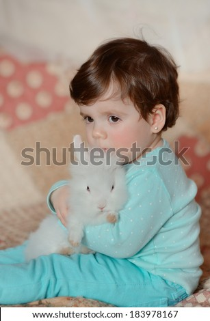little girl in a blue suit hugging a fluffy white rabbit