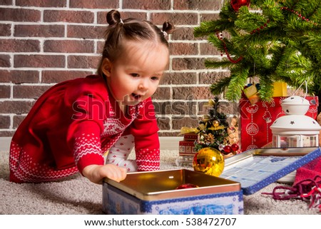 Little girl in a Christmas suit, at home waiting for Christmas next to the Christmas tree, opening presents