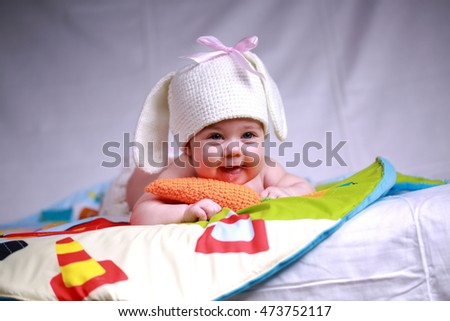 Little girl in a knitted cap with a carrot