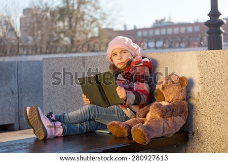 little girl in a pink beret sits on a bench in sunny autumn day with the book and a toy bear