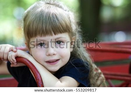 Little girl in an urban setting smiles at the camera. Portrait of happy, positive, smiling, playful  caucasian girl with beautilul hair