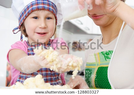 Little girl in baker hat and apron cooking in kitchen with mother