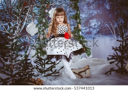 little girl in beautiful dress sitting on a swing in the Christmas winter forest