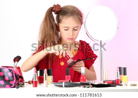 little girl in her mother's dress, is trying painting her face