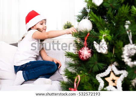Little Girl In Santa Hat Decorating The Christmas Tree