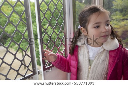 Little girl in the ferris wheel cabin. She's observing the high panoramic view