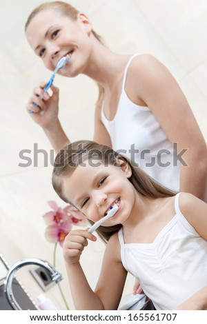 Little girl is happy to clean her teeth with her mom