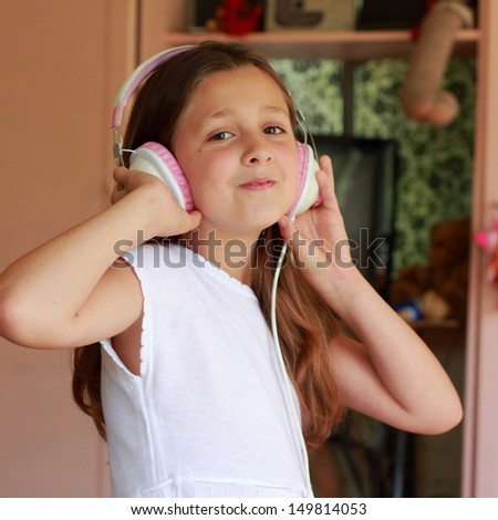 little girl is sitting on her bed listening to music on headphones at home