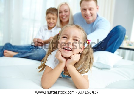 Little girl laughing with her family in the background
