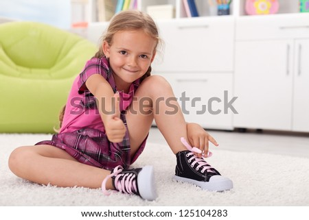 Little girl learning how to tie her shoes, being proud of herself