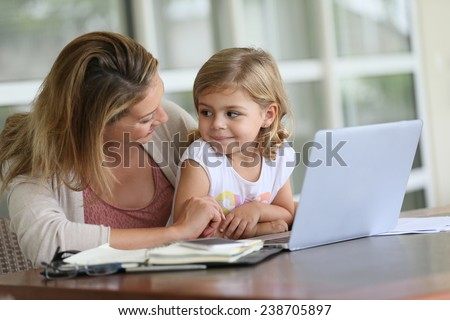 Little girl looking at laptop computer with her mom