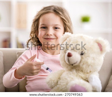 Little girl makes injection to teddy bear. Smiling and looking at the camera.