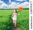 little girl on grass in summer day holds windmill in hand - stock photo