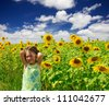 Little girl on sunflowers field - stock photo