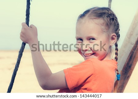 Little girl on the beach on a swing close up portrait.
