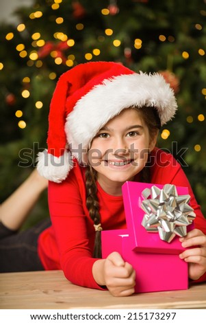 Little girl opening a gift at christmas at home in the living room
