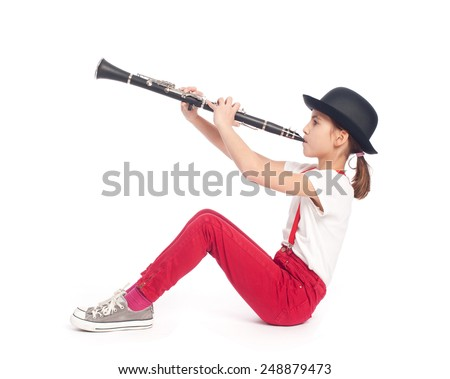 little girl playing clarinet on a white background