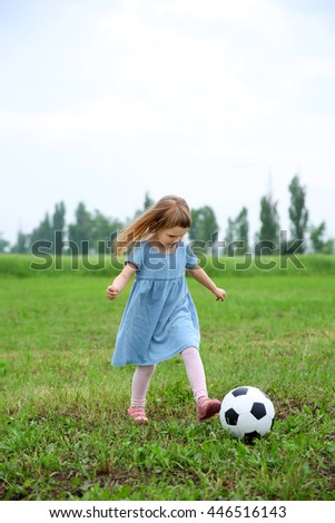 Little girl playing football outdoor