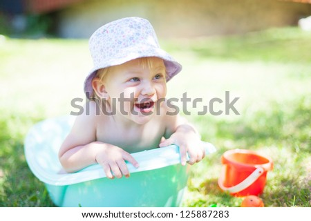 Little girl playing in the bathroom on the grass