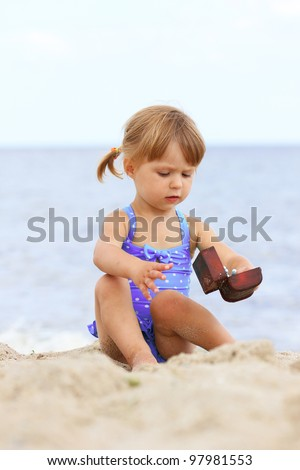 little girl playing on the shore of the sea