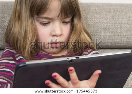 Little girl playing with a digital tablet at home on a sofa