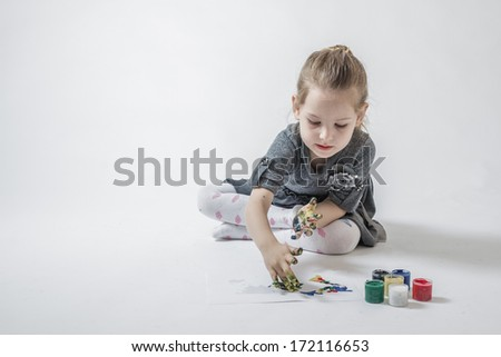 Little girl playing with colors by painting finger paints