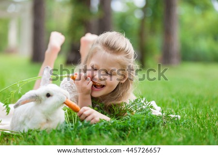 Little girl playing with white rabbit in summer day outdoor