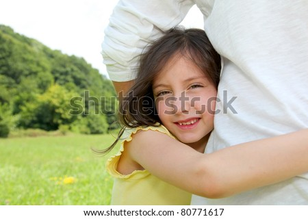 Little girl putting her arms around her father's waist
