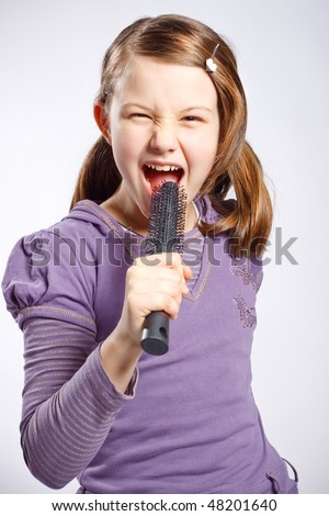 little girl singing using a hairbrush as microphone