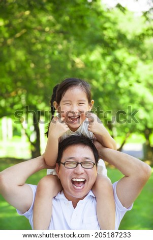 little girl sitting father shoulder and make a funny facial expression