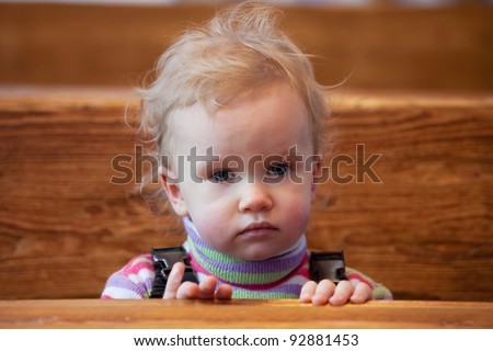 Little girl sitting in the warm at the table in a cafe