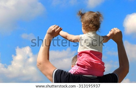 Little girl sitting on the shoulders of the  father