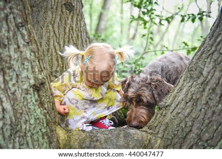 Little girl sitting on the tree  and playing with her dog in the wood on a sunny spring day. Best friends concept.Positive emotions.Outdoor activity and game with family pet on summer holiday.