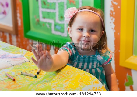 little girl smiling and waving to handle. selective focus