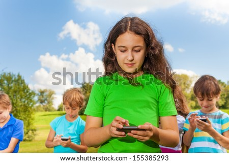 Little girl using her smartphone and texting standing in the park with clear sky
