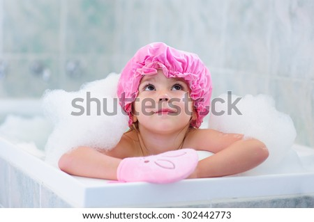 Little girl washing with a bubbles in bath in a hat