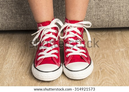 Little girl wearing a pair of red sneakers at home