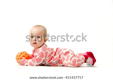 Little girl wearing white and pink pyjama, red socks is playing with her orange ball while lying on a belly