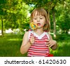 little girl with big sweet walks in park - stock photo