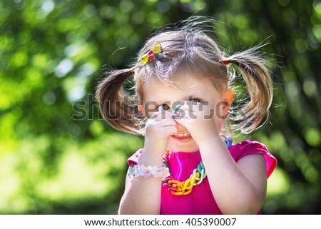 Little girl with bracelets in a park in summer
