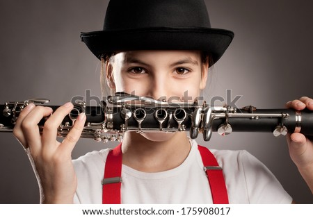 little girl with clarinet on a gray background