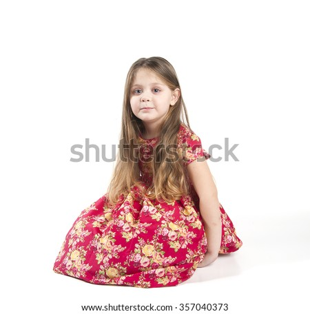 Little girl with long hair in a red dress. Studio photography on a white background. Age of child 4 years.