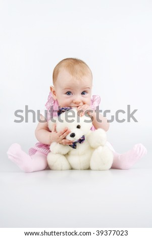 Little girl with plushy cuddle-bear and his ear in mouth,,on white background.