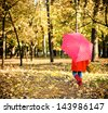 Little girl with polka dots umbrella walking through alley with fall foliage - stock photo