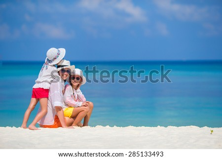 Little girls and mother on tropical white beach