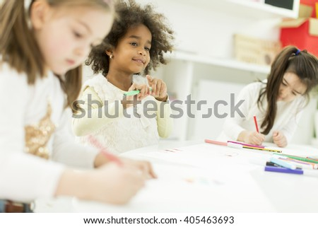Little girls drawing and learning in the kindergarten